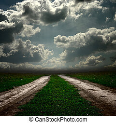 Road in field with stormy clouds