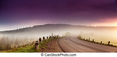 Road in mountain range panorama. Beautiful spring foggy morning in mountain serpentine