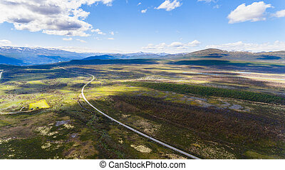 Road in Norway, mountains and blue sky, aerial shot from drone