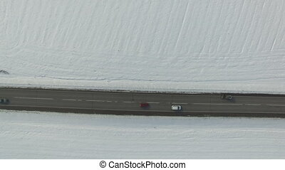 Road in snowed winter field with cars and trucks. Aerial...