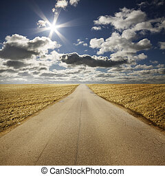 Scenic view of road receding past golden field in Summery countryside with blue sky, cloudscape and sunshine in background.