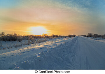 Winter road with snowy roadsides passing through the floodplain with traces of the protector at dawn