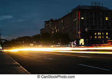 Road in the night city with light trails