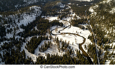 Road leads along a meandering river near McCall Idaho in winter