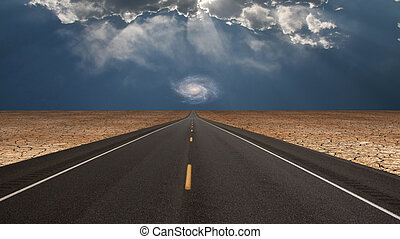 Road leads into desert toward galaxy above horizon