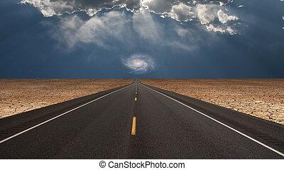 Road leads into desert toward galaxy above horizon