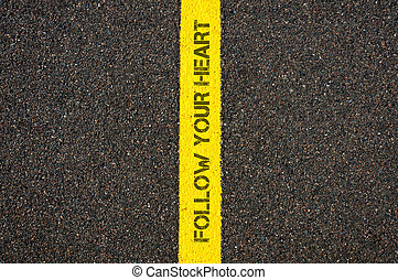 Road marking yellow line, text FOLLOW YOUR HEART
