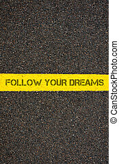 Road marking yellow line with words FOLLOW YOUR DREAMS