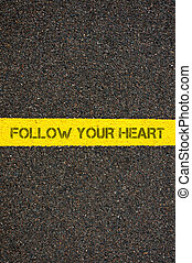 Road marking yellow line with words FOLLOW YOUR HEART