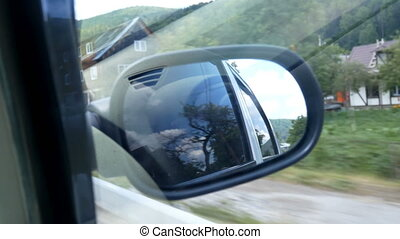 Road mirror car window - View of the road in the rearview...