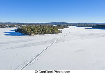 Road on lake in winter drone photo