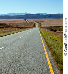 Road over farm lands in South Africa towards distant mountains