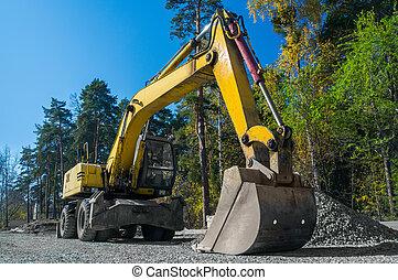 Road repair, asphalt laying. Yellow wheeled excavator