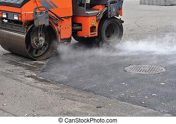 Road repair, compactor lays asphalt. Repair pavement and laying new asphalt patching method outdoors.
