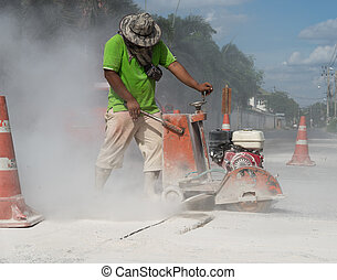Road Repair - Workers are cutting the asphalt on the road.