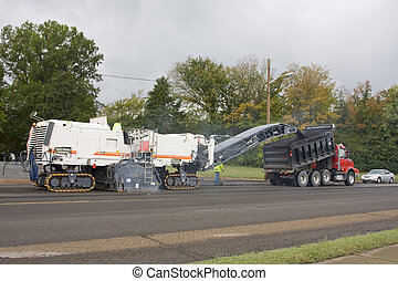 very large pavement removing machine is tearing old asphalt off the road and loading it to a dumptruck, asphalt will be recycled again to re-black top road