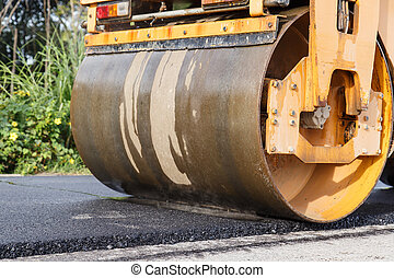 Road roller and asphalt paving machine at construction site