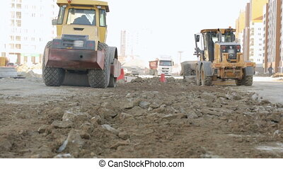 Road-roller and grader working at construction site