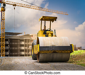 Road roller at construction site with cloudy blue sky