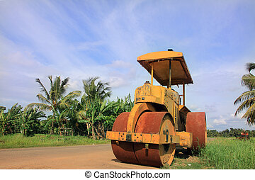 Road roller on farm background