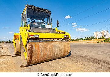 Road roller stands on asphalt surface.