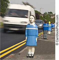 A set of blue schoolchildren safety bollards at the roadside with fast moving traffic passing them.