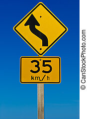 A road sign indicating a bend in the road with a reccomened speed of 35km/h. Isolated on a graduated blue background.