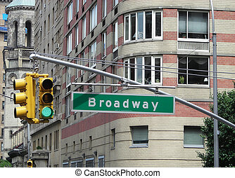 Road sign and green light on the street in New York City.