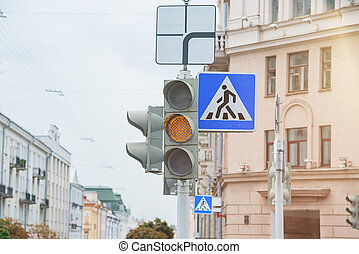 Road sign of a pedestrian crossing and traffic light with yellow light