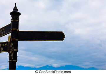 Road sign on the crossroads with blue cloudy sky in the background. Traveling concept with crossroad sign and blue background. Cloudy sky behind the road sign.