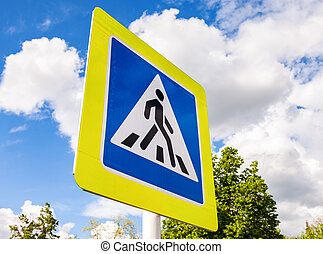 Road sign pedestrian crossing with clouds in background