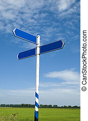 Road sign against a green field and blue sky