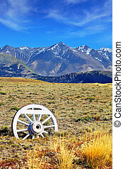 Road sign in the form of a wagon wheel. Gravel road in the...