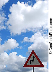 Road sign. Winding road, as life can also be a winding road. Nice sky in the background. Space for text.