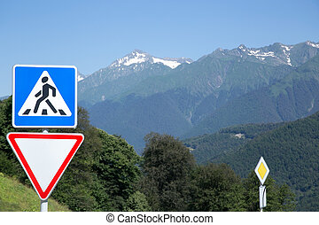 """Road signs in a mountain landscape. Pedestrian Crossing, Give Way, and Priority road. Resort """"Krasnaya Polyana"""", Sochi, Russia."""