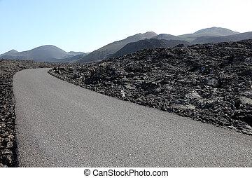 Road through a lava field the Montanas del Fuego on Canary Island Lanzarote
