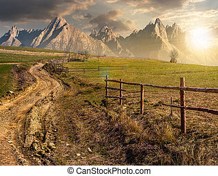 road through rural fields in mountains at sunset - road...
