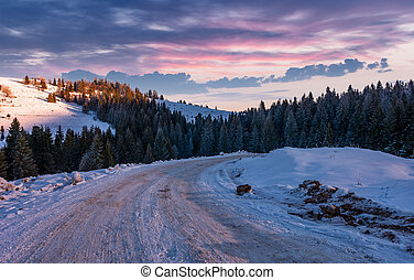 road through snowy hill side in to the forest - road through...