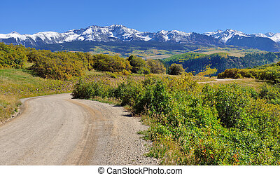 road through the mountains with colorful aspen during foliage season