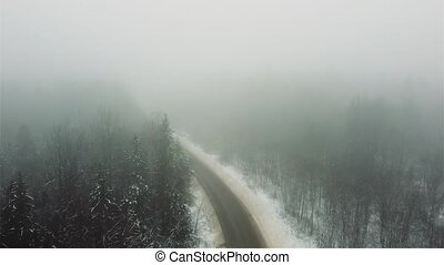 road through winter foggy forest aerial video.