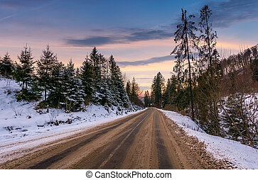 road through winter forest at down - road through winter...