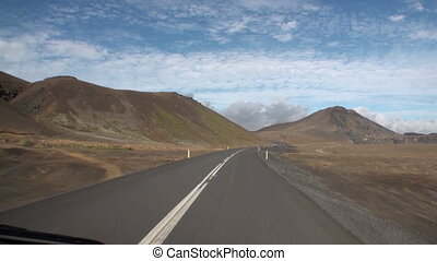 Road to background of mountains and clouds in the sky in Greenland.