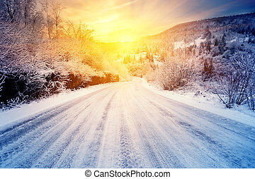 Road to the sunset in the winter mountains