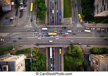 Road traffic with traffic jam on a highway overpass, top view. Two-level intersection of perpendicular highways with traffic on the bridge.