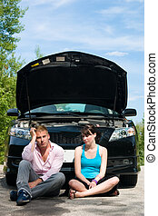 Road Trip - Car Broke Down - A young couple sits dejectedly...