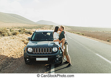 Road trip concept. Young hipster couple kissing in car on highway at sunset
