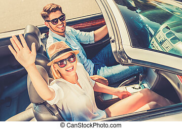 Road trip fun. Top view of cheerful young woman waving at camera while her boyfriend sitting near and driving their white convertible
