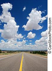 Long asphalt road with a cloudy sky