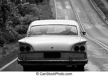 Road Trip - An old car during a road trip along a...