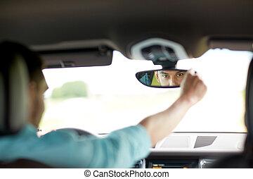 man driving car adjusting rearview mirror - road trip, ...